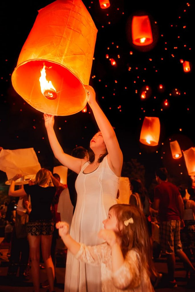 Family launching sky lanterns in Chiang Mai, Thailand.