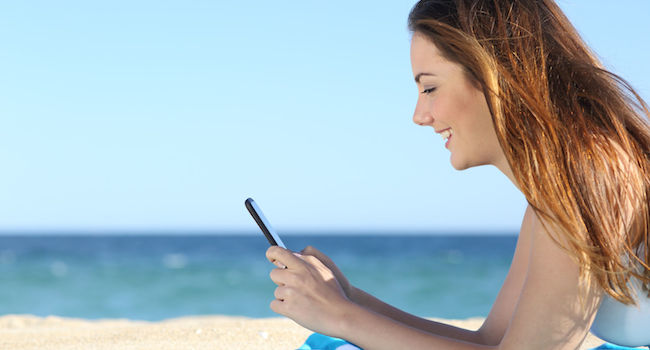 image of woman at the beach texting