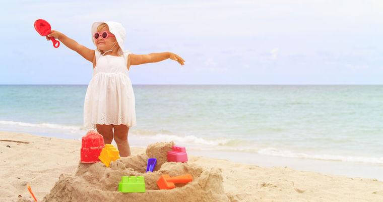 Girl on beach building a sandcastle