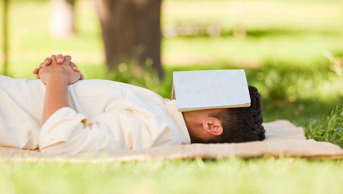 Man laying on grass with a book covering his face