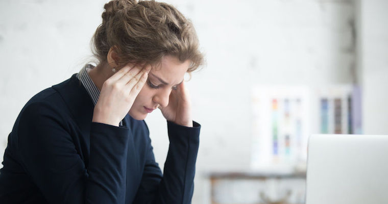 unhappy young woman sitting at desk frustrated at work