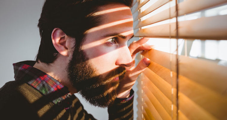 business man with a beard peeking through venetian blinds
