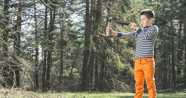 boy in orange pants with slingshot in the forest
