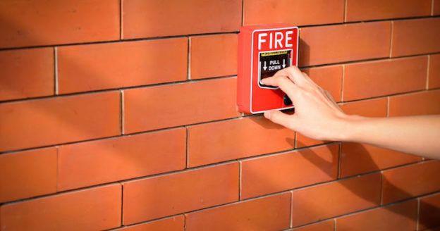 hand pulling a fire alarm brick wall backdrop