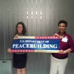 Debra Poss and Congresswoman Barbara Lee with the Department of Peacebuilding Banner