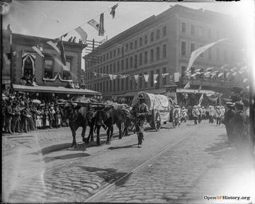 View southeast on Columbus (then Montgomery Ave.) to Admission Day parade, with oxen pulling covered wagon representing San Rafael parlor of NSGW. Montgomery Block in background. SFOpenHistory/ wnp15.1391.jpg <span>&copy; SFOpenHistory </span>