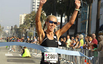 Laura crossing the finish line at the Santa Monica 10k Classic.