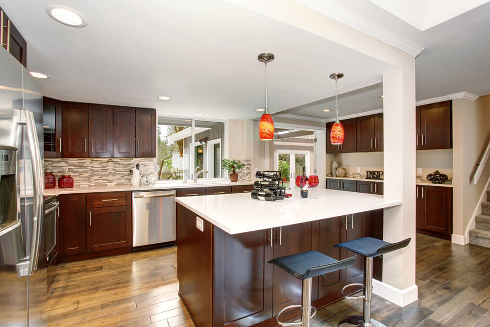 Small but bright color accents in orange and red match the warming and chocolate tones of the outstanding cabinets in this kitchen.