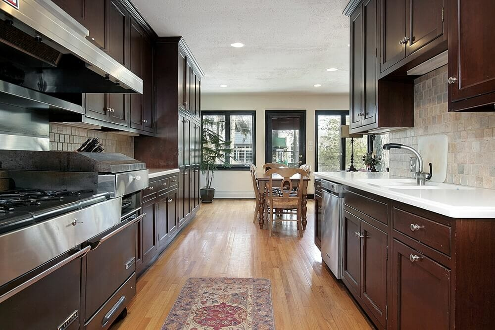 This parallel kitchen layout uses the light to prevent the narrow and dark room from becoming too darkening and harrowing. Natural light runs throughout the thoroughfare so that the dark cabinets don't sacrifice light in the room.