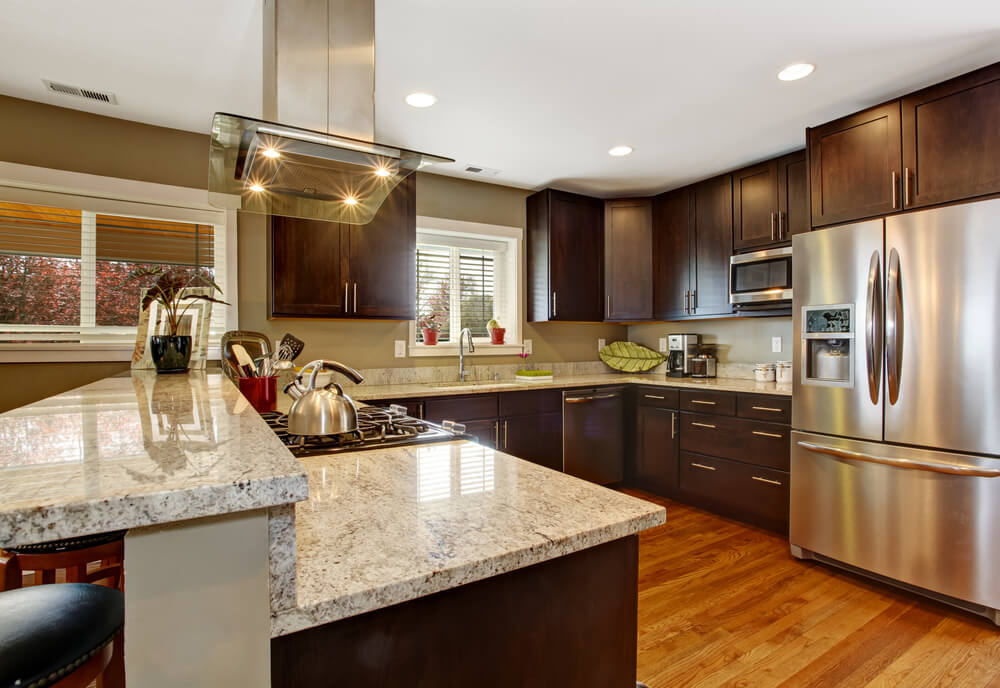 The mix of materials in this kitchen, including different shades of wood, granite, and stainless steel, bring lots of variety and comfort to this kitchen, making it a great mix of traditional and modern styles.