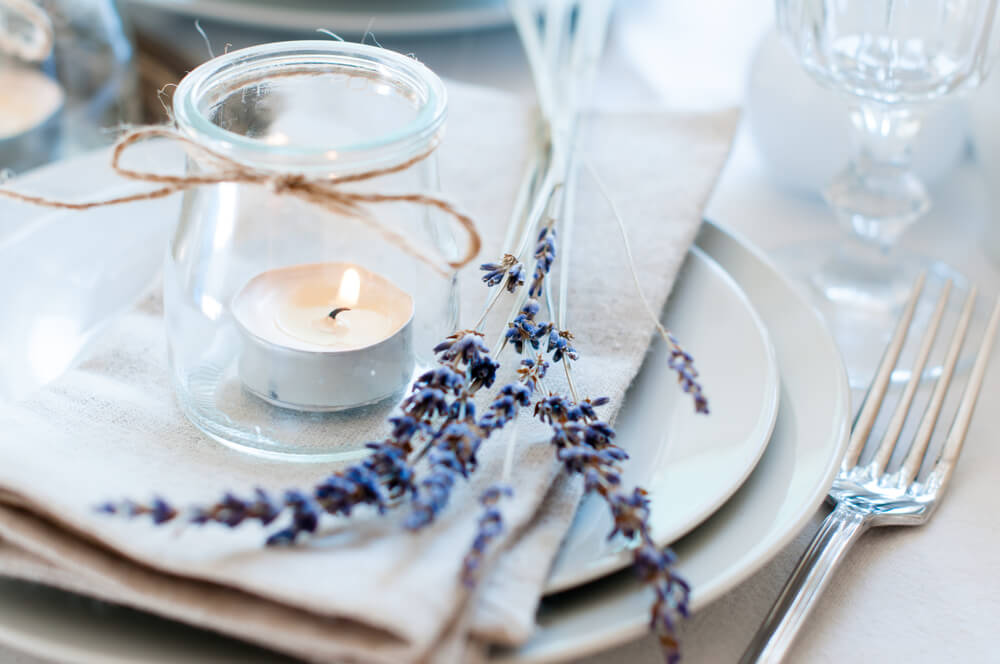A table setting that incorporates candles and the rustic charm of a lavender flower.