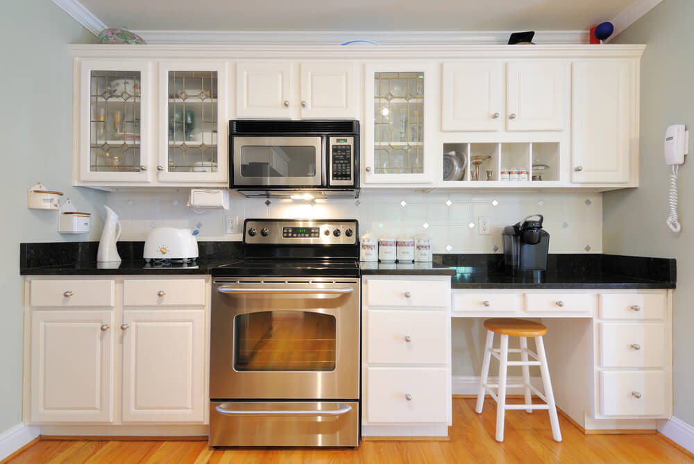 White cabinets mixed with cabinets with glass doors can make a small kitchen feel more open.