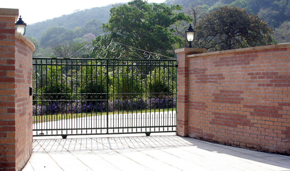 Solid brick fence with a wrought iron security gate is the pinnacle of security and style.