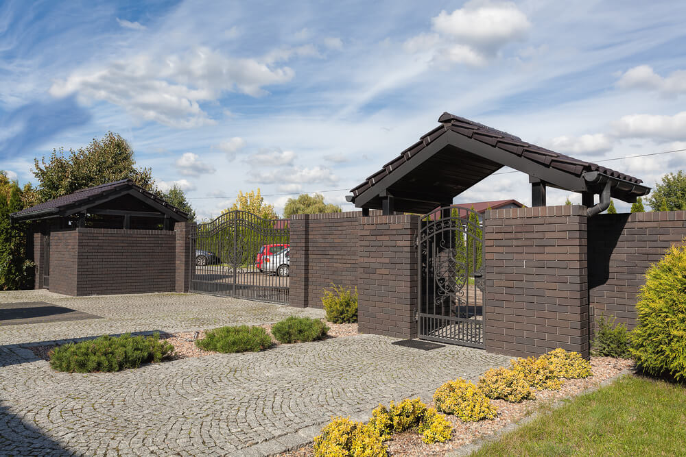 Brick fence designs come in many shapes and sizes. This modern dark, brick fencing mixed with a detailed iron gate give a traditional look and feel.