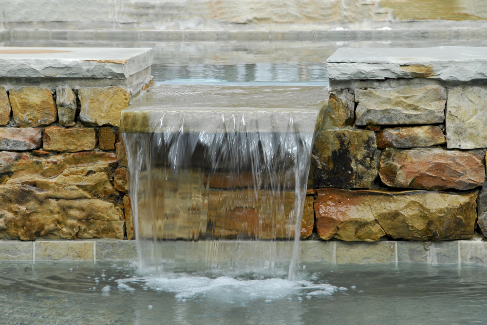 This water feature is actually created by using two pools with one slightly higher than the other. You create a cutout in the wall between and voila, you've got a waterfall that's fun and extremely easy.