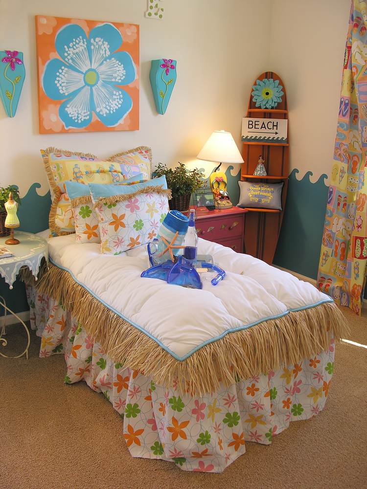 Here we've got a super beach themed bedroom but more for a teenager. The hula skirt bedspread, surfboard and bright colors give it a fun vibe but for a little younger crowd (and smaller pay scale).
