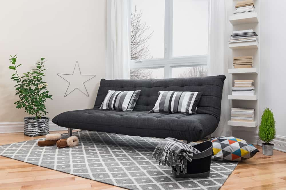 a black futon bed with stripped pillows