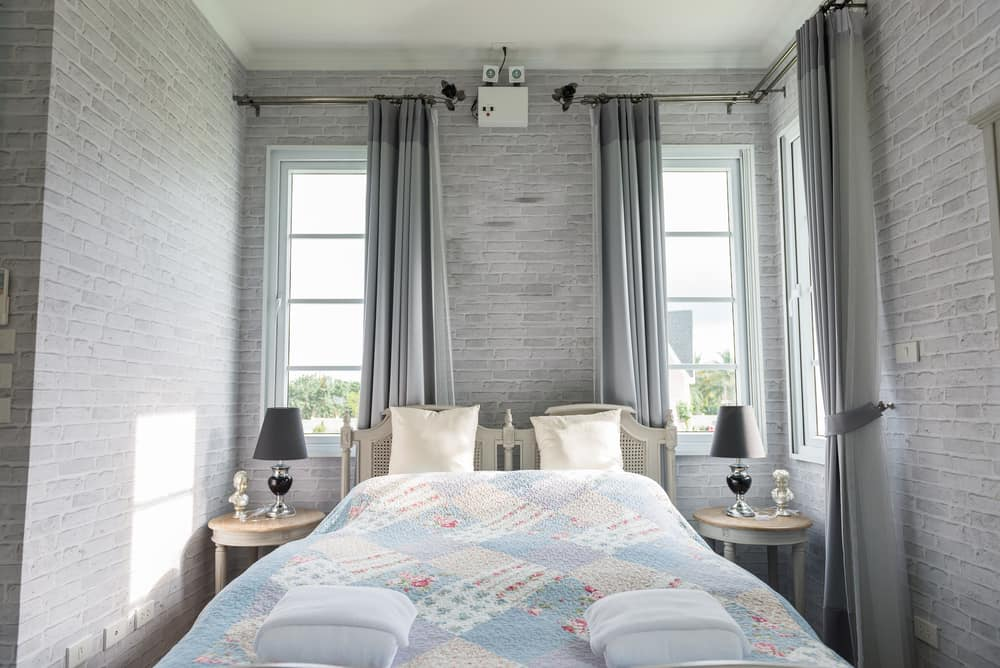 This room has a lot of gray in the background including the brick walls and the curtains. Instead of adding a whole lot of gray in the accessories as well, there's a little in the bed and end tables but plenty of other colors in the rest.