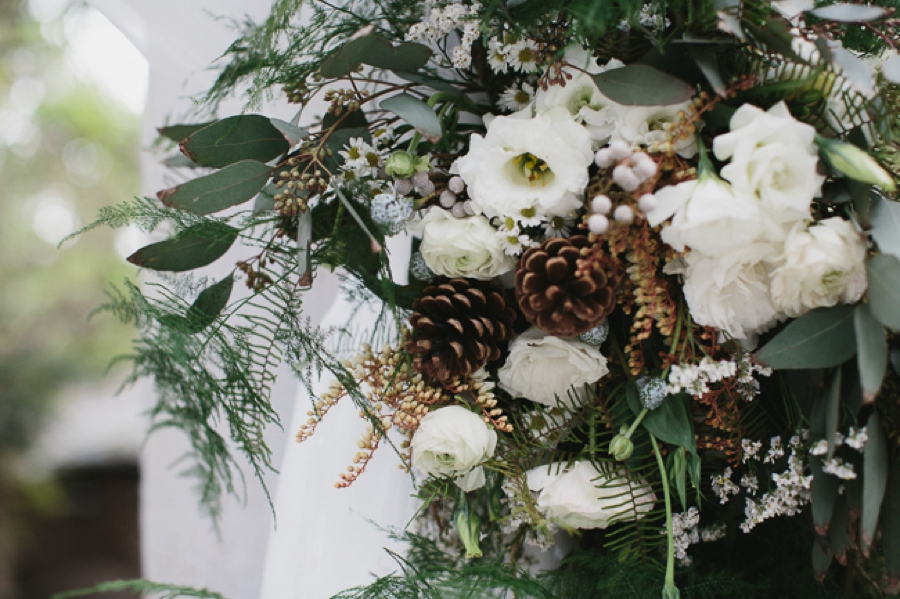 arch floral detail: white flowers with evergreen and pinecones