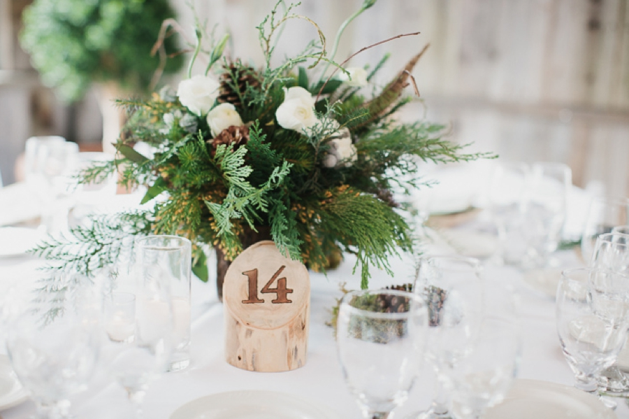reception centerpieces evergreen white and pinecone, wooden log table numbers