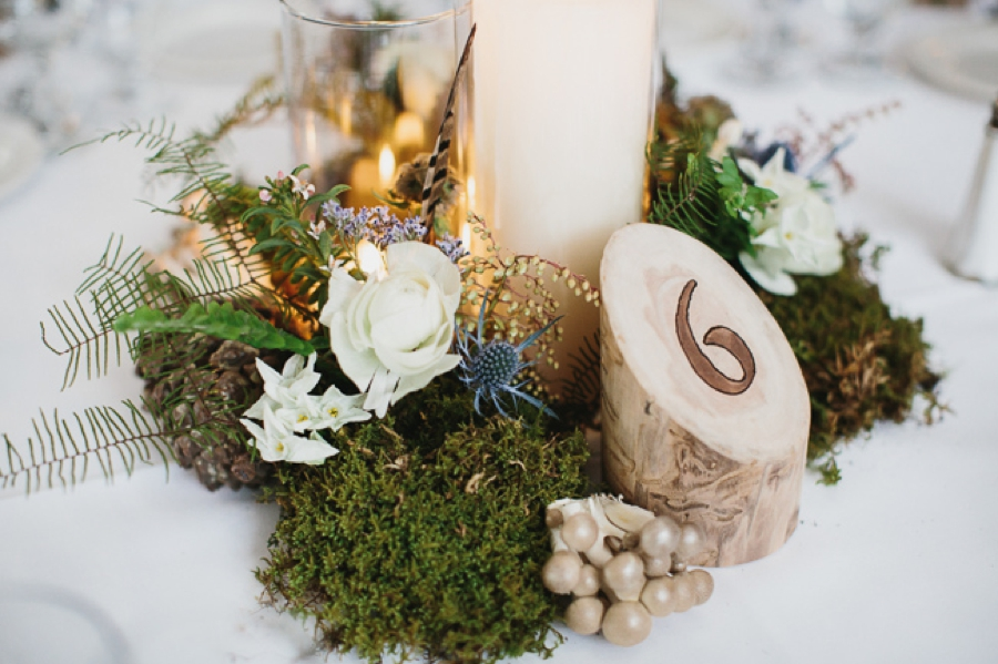 reception centerpieces moss pinecone and candles, log table numbers
