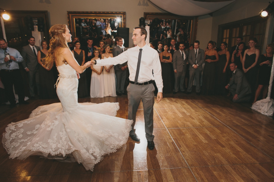 first dance twirl bride in strapless lace gown, groom in grey pants white shirt black tie