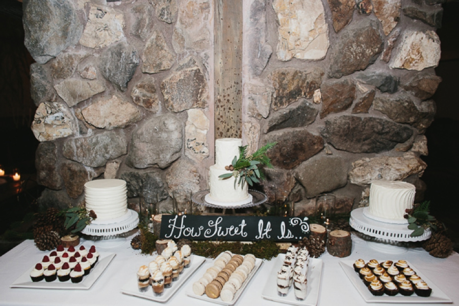 dessert table with two tier white wedding cake with greenery