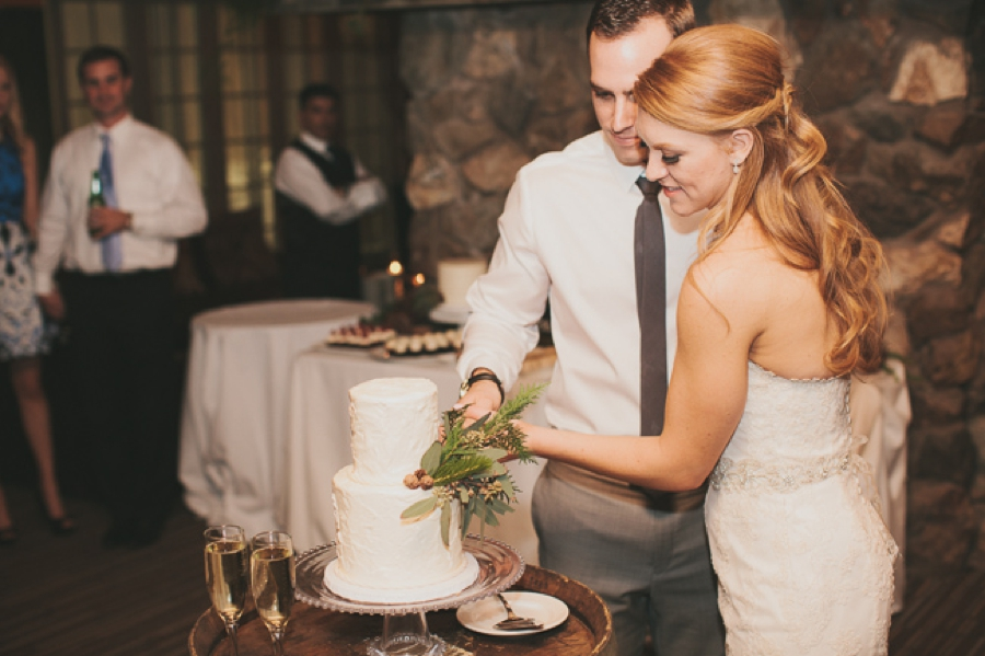 cake cut two tier wedding cake with evergreen sprig, bride in white lace strapless gown