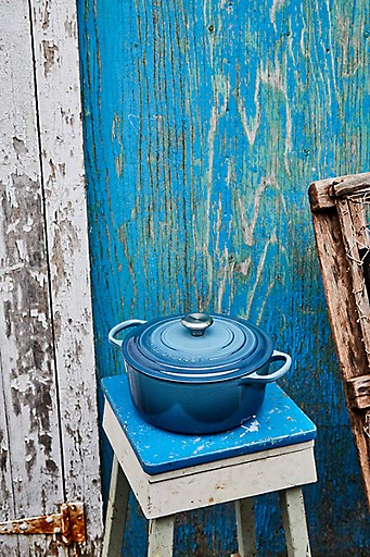 A Marine dutch oven on a stool beside a rustic sea-side shed