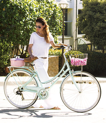 Woman walking beside a bike with Hibiscus Dutch Oven on back