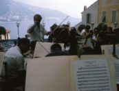 "1965 European Tour with Sasha conducting the Orchestra in Menton on the French Riviera | ""Sasha used his personal linguistic invention, Schmoekadores, in many different ways to mean a variety of things.  He might say 'Play this passage with a little more Schmoekadores,' meaning a little more emotion.  Or, 'Let's stop the Schmoekadores and get back to work.' Or, 'The greatest pleasures in life are making music, making chicken soup, and making Schmoekadores!'"" -Isidore Cohen"