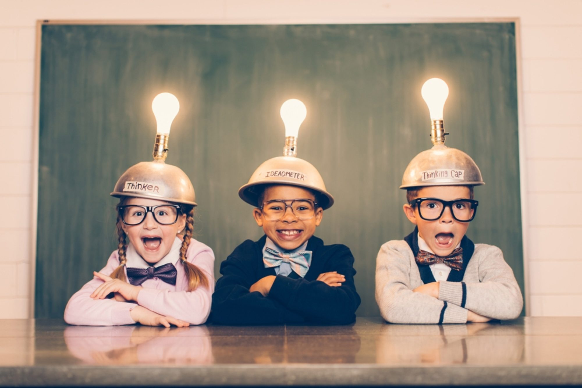 Three smiling young kids wearing lightbulb helmets