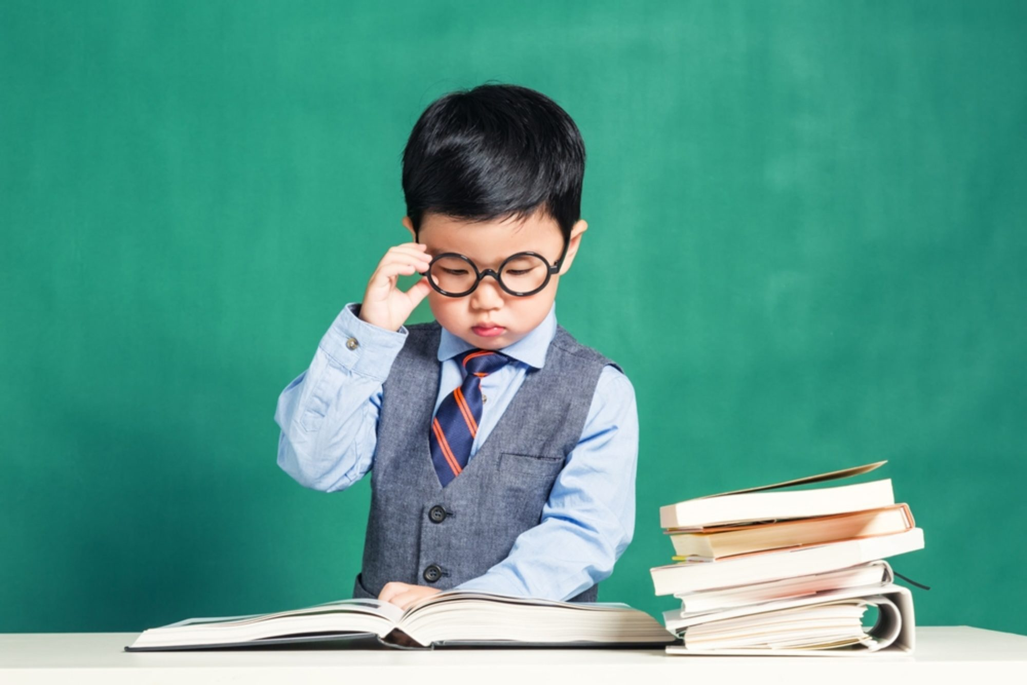 Boy in glasses reading a pile of books