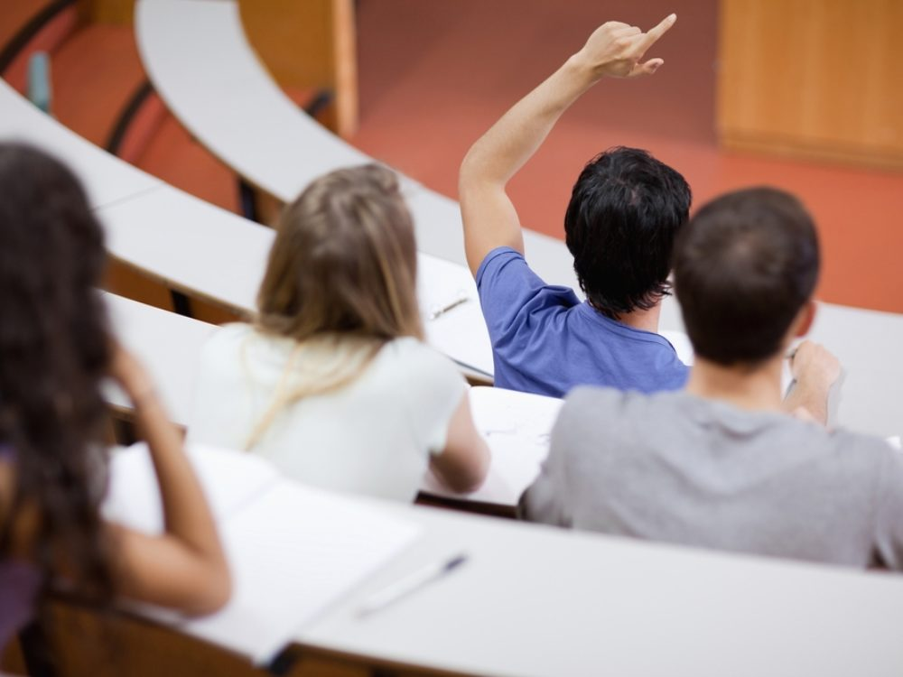 Students in a college class, one with raised hand