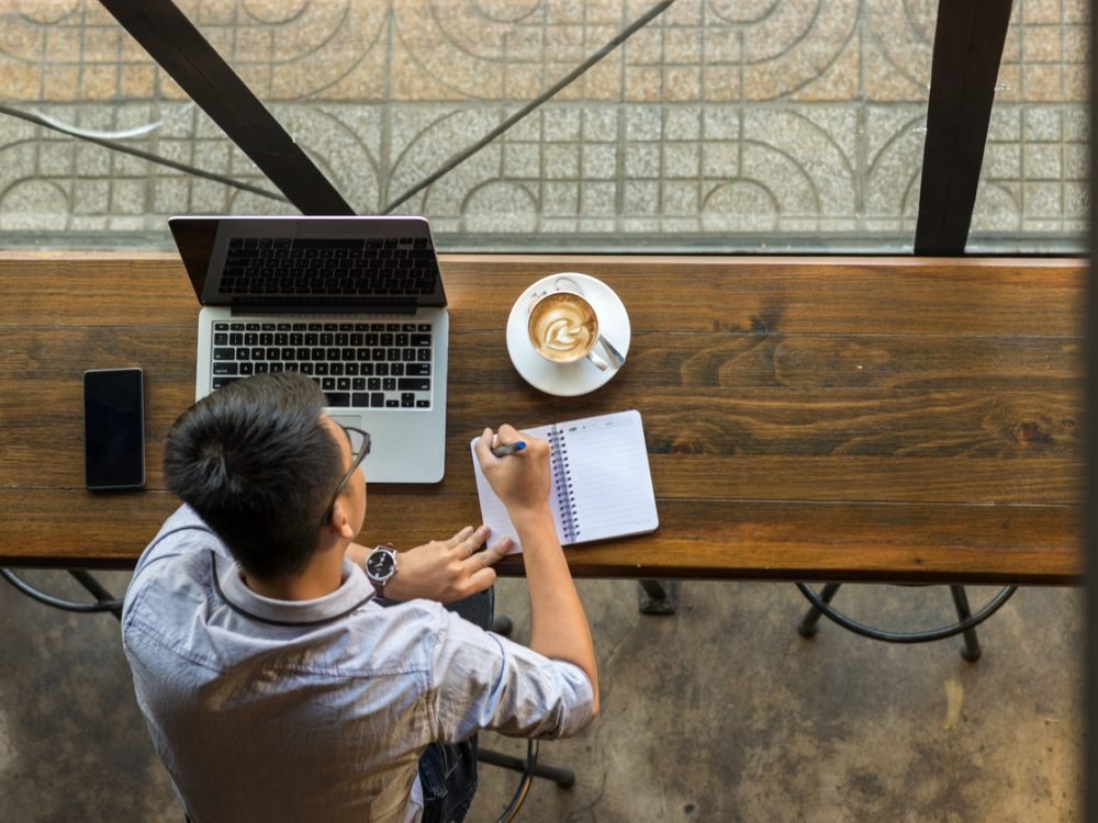 Young man in cafe with laptop, phone, notebook and coffee