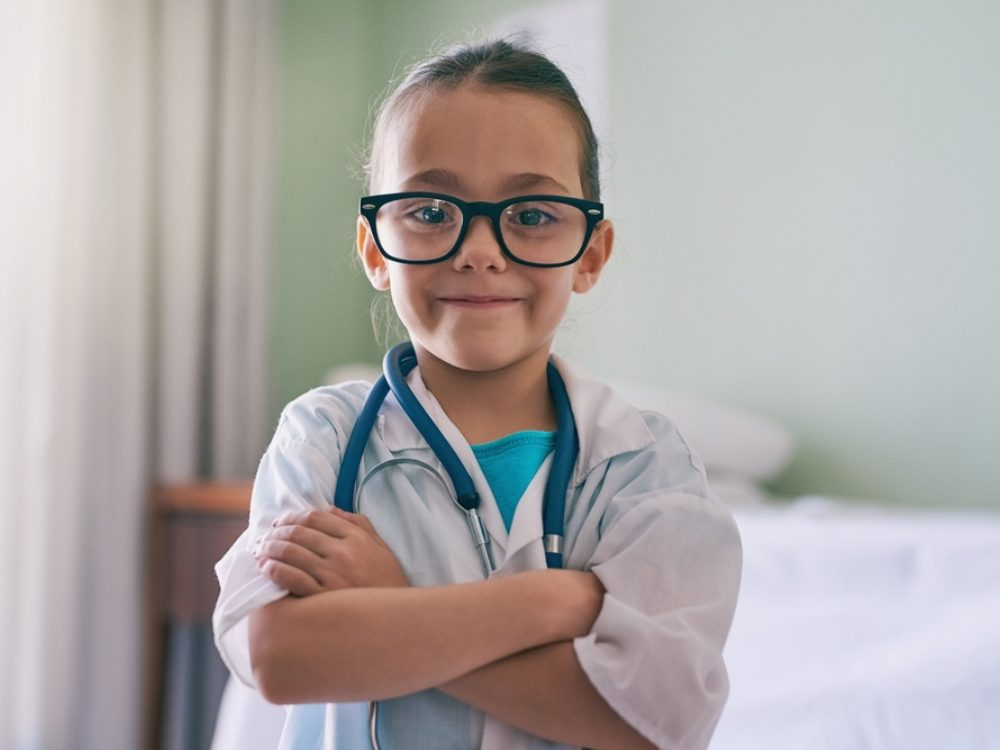 Young girl in glasses and doctor's uniform