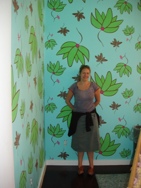 Kat in front of kids' wallpaper she designed