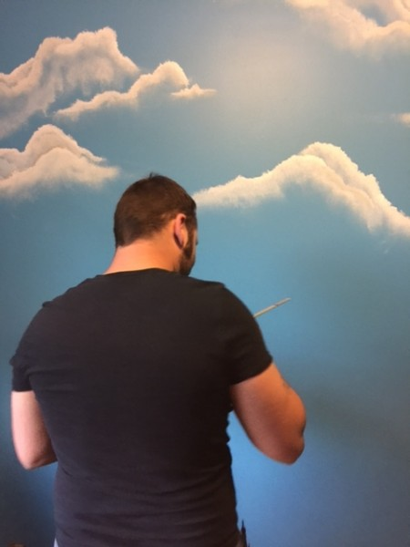 Chris having fun painting clouds on the wall