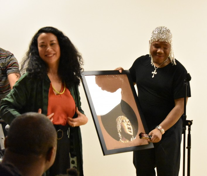 Kristina presenting our friend TJ with a poster we designed for him and the Black History Month Event at our space
