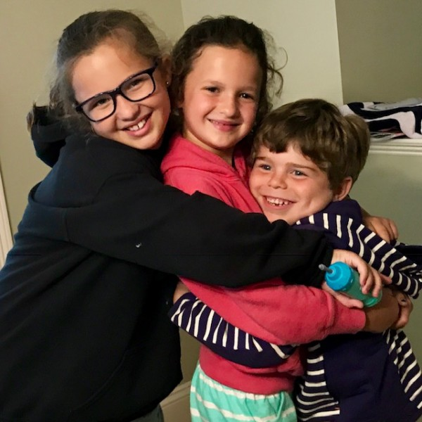 Eliot in a bear hug with cousins Phoebe and Anna