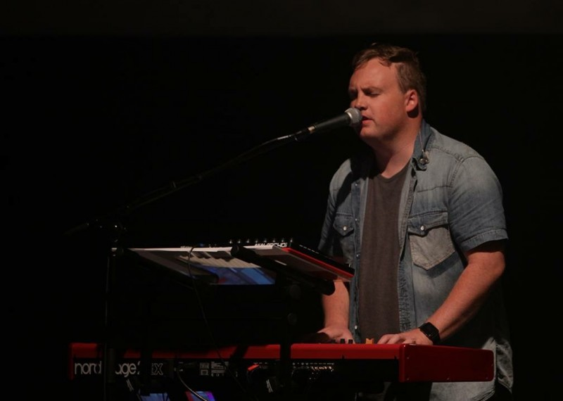 Fred leading worship and playing keys at church.