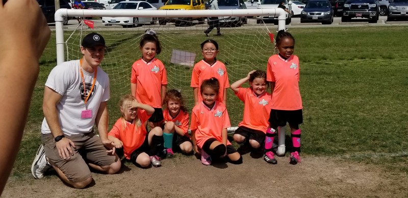 Adam posing with the soccer team after their last game. Emberlyn is next to him.