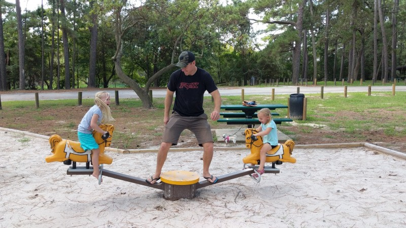 Adam is helping Emberlyn and Everly use the teeter totter at a local park.