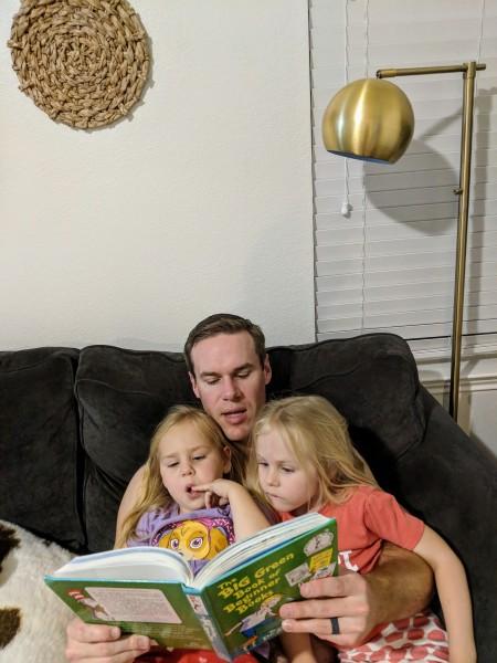 Adam reading books to the girls.