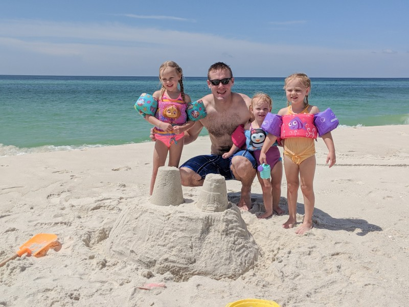 Adam and the girls posing with their sand castle. Navarre Beach.