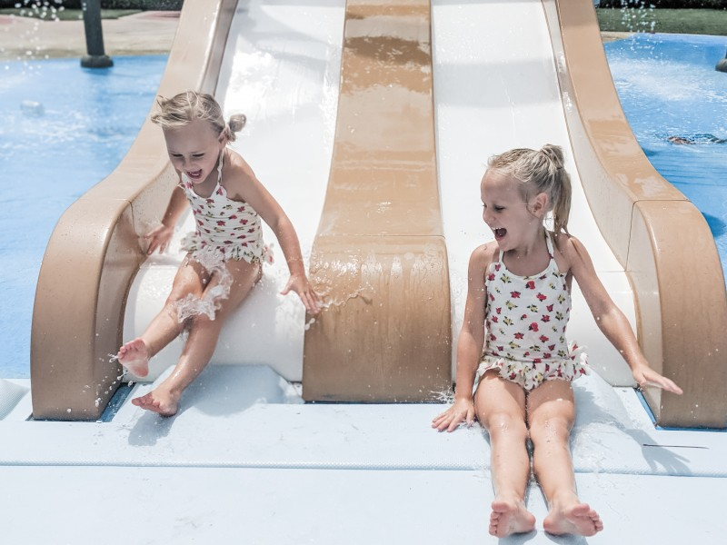 Racing down the splash pad slide together. Ember and Ever.