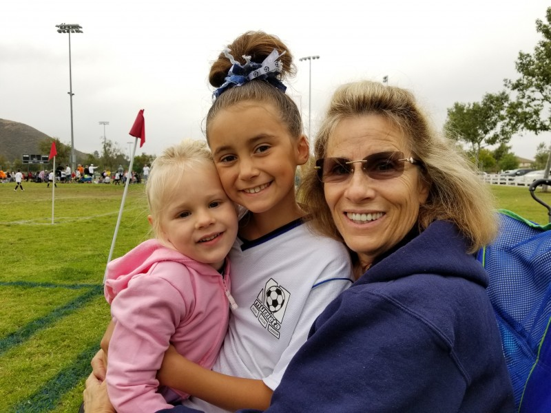 Ember is watching cousin Saylor's soccer game with Grandma Sharol.