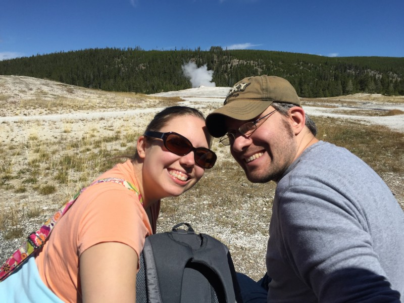 Annie & Paul pose in front of Old Faithful waiting for it to erupt