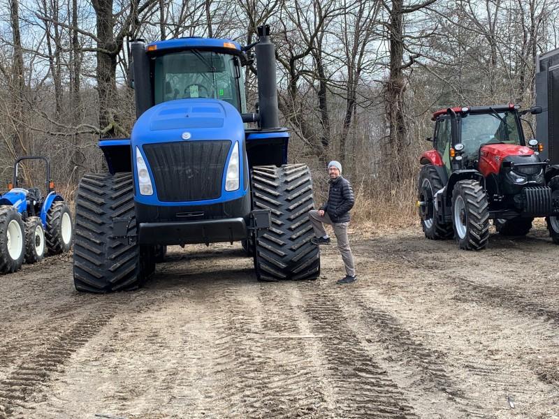 Ben, posing, before loading tractors for work