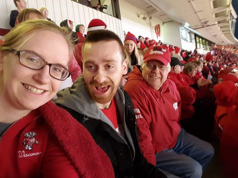 Maria, her brother and Craig's dad cheering on the Badgers!